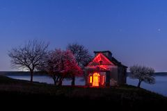 Deserted church and blooming trees nightscape royalty free stock photography