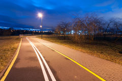 Deserted city bicycle path in the autumn evening Royalty Free Stock Photo