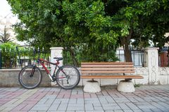 On a city street bicycle next to an empty bench royalty free stock images