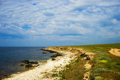 Deserted coast of the black sea with picturesque clouds. Royalty Free Stock Images