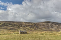 Deserted Cottage. A Deserted Cottage Next to a Hill royalty free stock photo