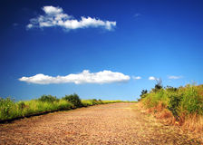 Deserted country road. Under beautiful blue sky stock photo