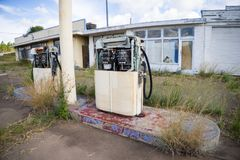 Deserted Petrol Station. A deserted fuel or petrol station with the petrol pump in the foreground. The pumps are rusted and broken royalty free stock photography