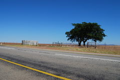 Deserted highway. Through countryside under blue sky Stock Images