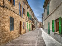 Deserted narrow paved road or lane in a town. With quaint old double storey houses with painted wooden shutters in a receding view royalty free stock photo