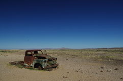 Deserted old Rusty car wreck deserted in the Namibia desert near death Valley signifying loneliness. Stock Photos