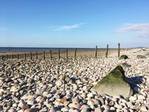 Pebbled beach with old sea defence in Wales UK Stock Photos