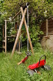 Deserted playground. Abandoned courtyard playground with a small red toy car in the foreground and a wooden swing in the back Royalty Free Stock Images