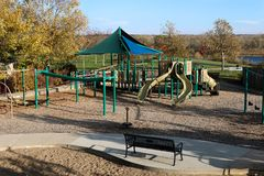 Deserted playground on a beautiful fall day. Blue sky and colorful trees, green grass, sand, benches, slides, swings, sidewalk, path, lake Stock Photography