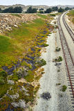 Deserted railroad tracks along pacific coastal area leading into the horizon. Cool morning near the abandoned Army post Fort Ord, in Monterey County, California royalty free stock photo