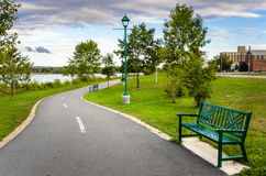 Deserted Riverside Path. Deserted Winding Riverside Path Lined with Benches and Trees In Fredericton, New Brunswick, Canada Royalty Free Stock Photography