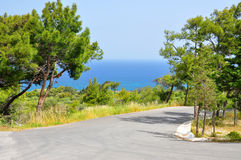 Deserted road. Near blue sea Royalty Free Stock Images