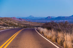 Deserted road curving to the mountains. Deserted major road going to the mountains, curving in the distance Royalty Free Stock Images
