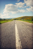 Deserted road leading to the mountains Stock Photos