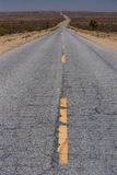 A deserted road in the middle of the desert Royalty Free Stock Photos