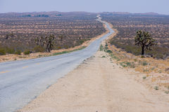A deserted road in the middle of the desert Royalty Free Stock Image