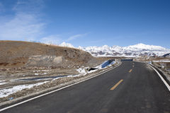 Deserted road and snowy mountains Royalty Free Stock Image