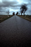 Deserted road under stormy sky Royalty Free Stock Images
