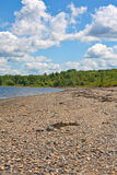 Deserted rocky beach. A rocky beach with distant woods and a blue cloudy sky in Stockton Springs Maine Stock Photo