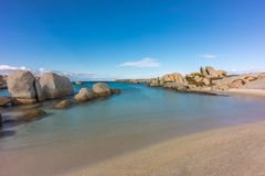 Rocky coastline and sandy beach at Cavallo island near Corsica. Deserted sandy beach and boulders on coast of Cavallo island near Corsica in France with blue Stock Image
