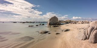 Rocky coastline and sandy beach at Cavallo island near Corsica. Deserted sandy beach and boulders on coast of Cavallo island near Corsica in France with Royalty Free Stock Photography