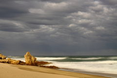 Deserted sandy beach with dark cloudy sky. Long exposure of a sloping sandy beach with a dark clouded sky and a hint of the glow of the sunset behind the royalty free stock photos