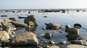 Deserted shore of the sea, full of calm, rocks in the water. Stones in the clear water of the sea. Calm and silence. Pure light horizon Royalty Free Stock Photos