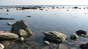 Deserted shore of the sea, full of calm, rocks in the water. Stones in the clear water of the sea. Calm and silence. Pure light horizon Stock Photos