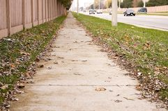 Deserted sidewalk. A long deserted sidewalk within a city shot in autumn Stock Photo