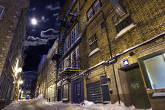 Deserted Street. Empty street in a winter night highlighted by moon Stock Photo