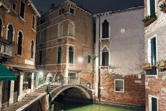 Deserted street with a marble arc bridge over a water channel il. VENICE, ITALY - DECEMBER 23, 2017: Empty street with a bridge over a water channel in Venice in Royalty Free Stock Images