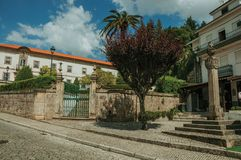 Old buildings behind stone wall with iron gate and pillory. Deserted street with old buildings behind stone wall with iron gate and pillory, in a sunny day at stock photos