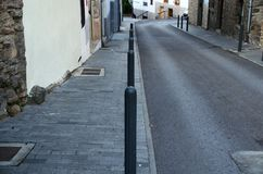 Deserted street with sidewalk and perfectly aligned bollards royalty free stock photo