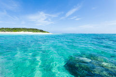 Deserted tropical island beach and clear blue wate Stock Images