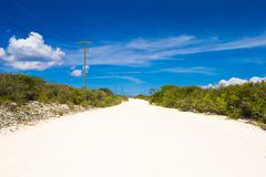 Deserted tropical road with white sand on Royalty Free Stock Image