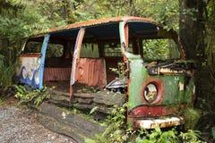 Deserted Volkswagen van in the Tofino Botanical Gardens. Overgrown abandoned Volkswagen bus in the Tofino Botanical Gardens stock images
