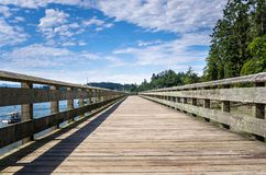 Deserted Wooden Boardwalk under Blue Sky With Clouds on a Summer Morning. Deserted Wooden Boardwalk along the Shore of a Bay on a Sunny Summer Morning. Sooke, BC royalty free stock images
