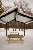 Deserted wooden picnic table and bench in snow. Deserted wooden picnic table and bench under a covering roof in winter snow in a wooded park or rest stop Royalty Free Stock Photos