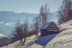 Deserted wooden shack. Deserted weathered wooden ramshackle. Winter rural landscape with old rustic wooden cowshed in Pestera village, Rucar-Bran pass, Brasov Royalty Free Stock Image