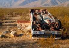 Deserted wrecked car in the desert. With bullet holes in the door Royalty Free Stock Image