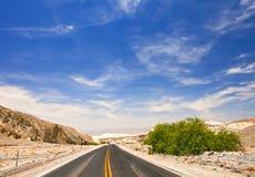 Desertera vägen och blå himmel i den Death Valley nationalparken Arkivfoton