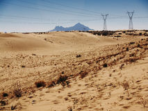 Desertic High Voltage Towers. High Voltage Towers in the desert with power lines Stock Photos
