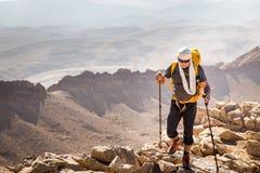 Deserto corrente di camminata della scogliera della montagna di viaggiatore con zaino e sacco a pelo turistico della guida, Fotografia Stock