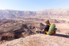 Deserto di riposo di seduta della pietra del bordo della montagna di viaggiatore con zaino e sacco a pelo dell'alpinista Fotografie Stock