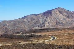 Deserto e cielo blu dell'automobile della montagna della strada Immagini Stock