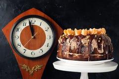 Deseru tort z czekoladowym lodowaceniem dekorował z tangerines na czarnym tle Zegarowy drewniany zdjęcie royalty free