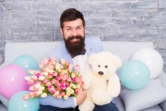 She deserve all best. Romantic man with flowers and teddy bear sit on couch with air balloons waiting girlfriend. Romantic gift. Macho ready romantic date. Man royalty free stock photos