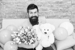 She deserve all best. Romantic man with flowers and teddy bear sit on couch with air balloons waiting girlfriend