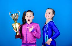 Deserved award. Girls athletic kids celebrate victory. Athletic girls with golden goblet. Win championship. Our team. First place. Children gymnasts athletic royalty free stock photography