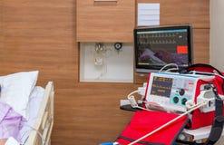 Desfibrilador na sala de ICU no hospital com equipamentos médicos Fotografia de Stock Royalty Free